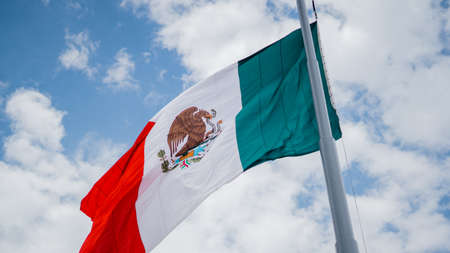 Mexican Flag Waving in the Wind and Blue Cloudy Sky as the Background