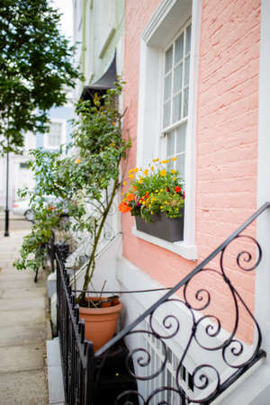 Pink and White House Decorated with Flowers and Plants Stock Photo