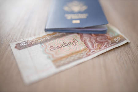 United States of America Passport on top of a Fifty Burmese Kyats Bill