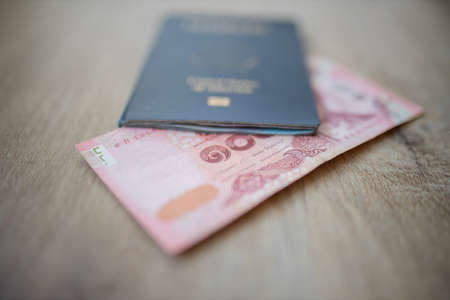 100 Thai Baht Bill Partially Inside a United States of America Passport