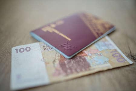 100 Moroccan Dirhams Bill Partially Inside a Sweden Passport
