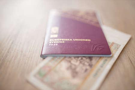 Sweden Passport with a Fifty Burmese Kyats Bill Partially Inside