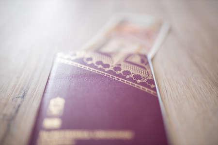 Sweden Passport with a Blurry Fifty Burmese Kyats Bill Partially Inside