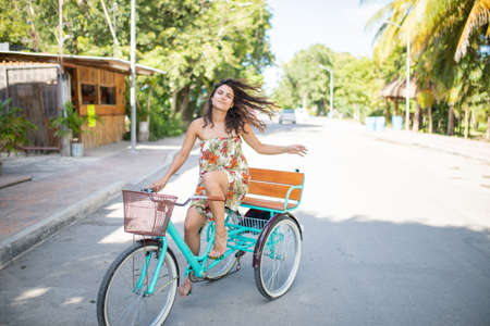 Beautiful woman wearing a dress and riding an adult tricycle Standard-Bild