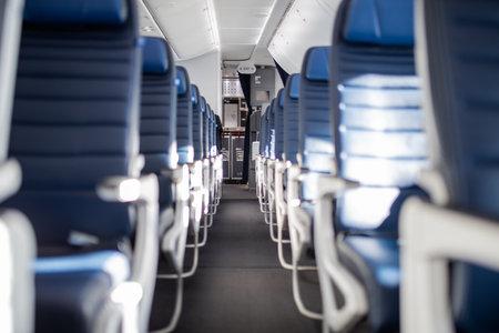 Empty dark blue passenger airplane seats in the cabin.
