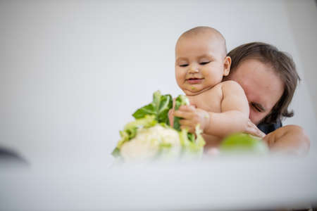 Father lovingly holding and kissing his baby daughter above a table Stockfoto