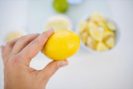 Female hand holding a lemon above slices of limes and lemons