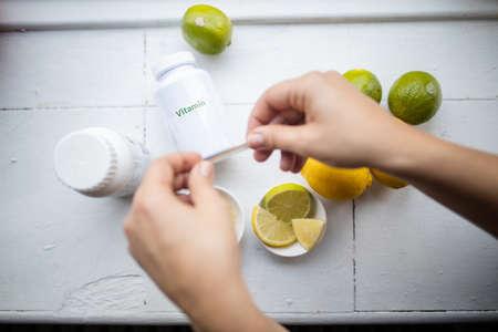 Female hands above vitamin bottles, lemons and limes