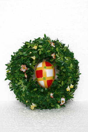 eastertime: easter wreath and painted egg isolated on white