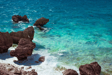 White waves breaking on the sea and the red rocks of Okinawa transparent emerald green