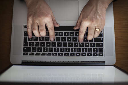 A married middle aged woman writing on laptop