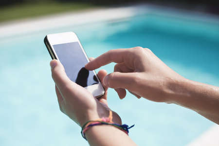 A woman using a smartphone in a swimming pool Stock Photo
