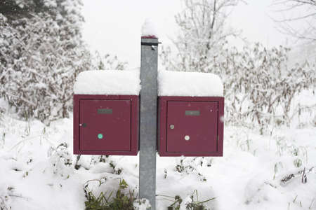 Two red boxes inthe snow on a winter day