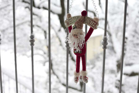 A santa claus puppet holding the text welcome winter on his head on a snowy background