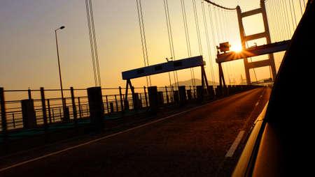 orange sunset: car on the bridge with orange sunset view