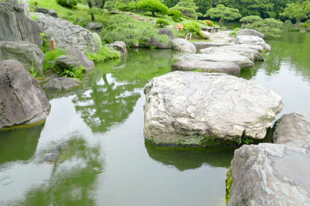 stone bridge green trees water pond in the japanese zen garden photo - Japanese Garden Stone Bridge