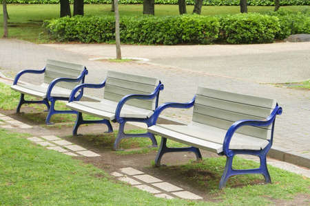 arm bands: Wooden benches with blue arm bands in the public park