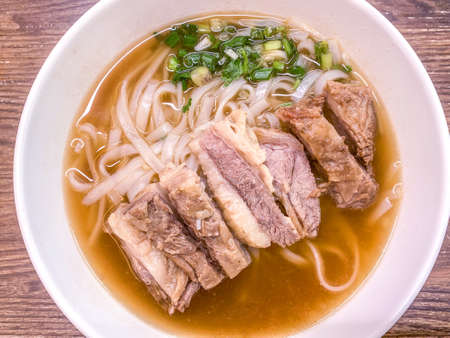 The bowl of Chinese food meat noodles on wooden table Banco de Imagens