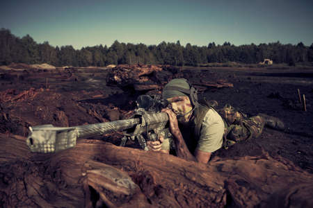 sniper training: Special forces soldier with sniper rifle observing terrain in apocalyptic scenery  Illustration photo