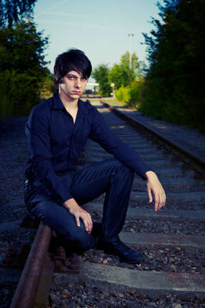 dolorous: Moody young man acting his emotions on outdoor location when posing for illustration photos. Stock Photo