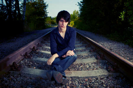 dolorous: Moody young man acting his emotions and assuming depression and suicide ideas on outdoor location when posing for illustration photos.