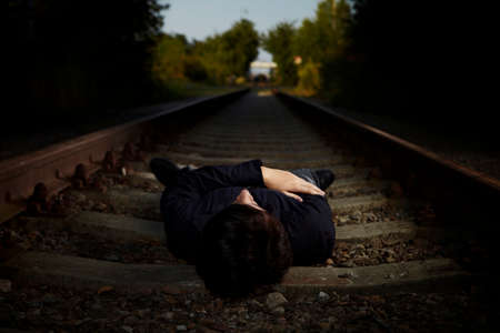 heartsickness: Moody young man acting his emotions and assuming depression and suicide ideas on outdoor location when posing for illustration photos.