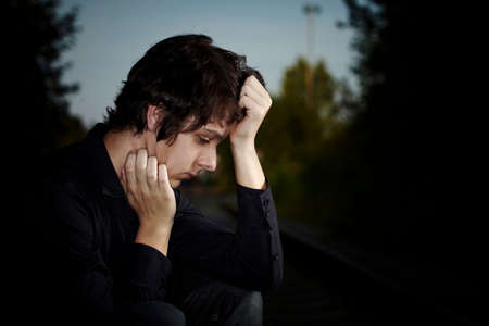 heartsickness: Moody young man acting his emotions and heartsickness on outdoor location when posing for illustration photos. Stock Photo