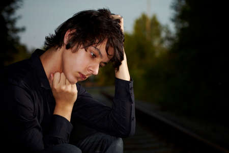 Moody young man acting his emotions and heartsickness on outdoor location when posing for illustration photos. Stock Photo