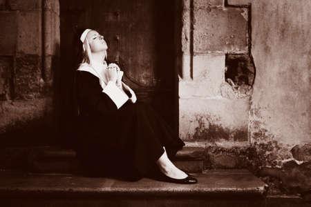 sotana: Buena chica posando como una monja sentada por la iglesia en Praga para fotos estilo religi�n.