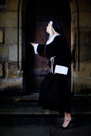 crist: Nice girl posing like a nun walking by church in Prague for religion style photos.
