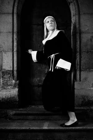 toog: Mooi meisje die zich voordeed als een non wandelen door de kerk in Praag voor de godsdienst stijl foto's.