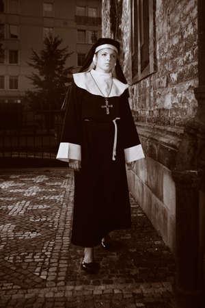 sotana: Buena chica posando como una monja caminando por la iglesia en Praga para las fotos de estilo religi�n.