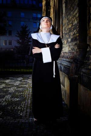sotana: Buena chica posando como una monja caminando por la iglesia en Praga para fotos estilo religi�n.
