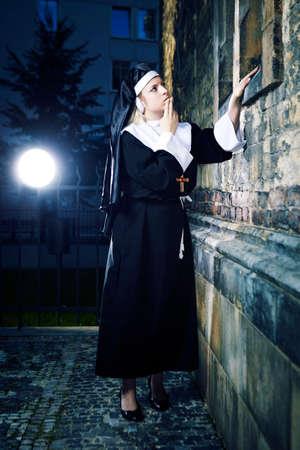 vestal: Nice girl posing like a nun nearby church in Prague for religion style photos. Stock Photo