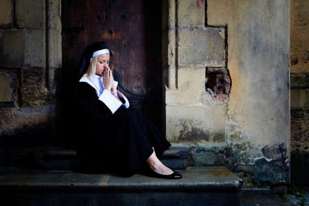 vestal: Nice girl posing like a nun sitting by church in Prague for religion style photos.