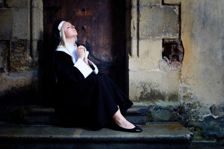 sotana: Buena chica posando como una monja sentada por la iglesia en Praga para las fotos de estilo religi�n.