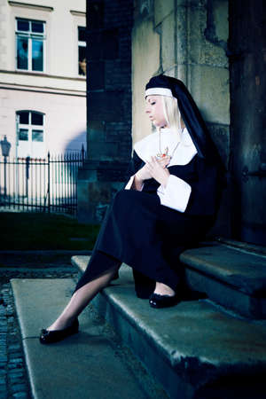 crist: Nice girl posing like a nun sitting by church in Prague for religion style photos.