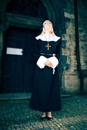 crist: Nice girl posing like a nun nearby church in Prague for religion style photos. Stock Photo