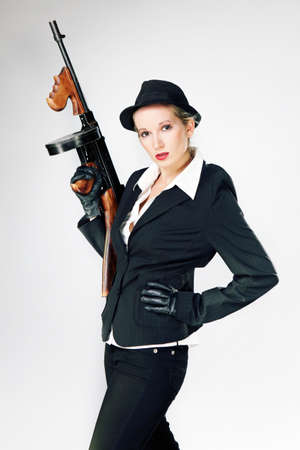 tommy: Mafia style fashion studio portrait - nice young woman posing with \Tommy\ gun for figure and portrait photos in retro criminal style.