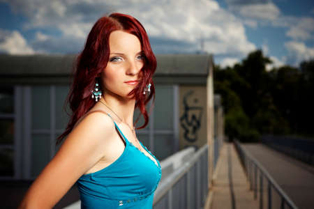 guardrail: Nice redhair lady posing in summer light on outdoor location - river floodgate in several dress styles.