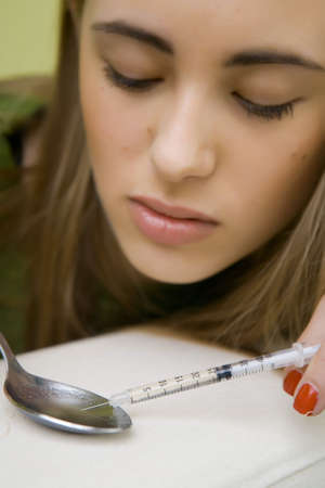 Drugs - young woman posing as a drug consumer on illustration photos with syringe