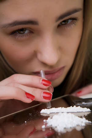 Girl posing in studio as a cocaine consumer Stock Photo - 34037774