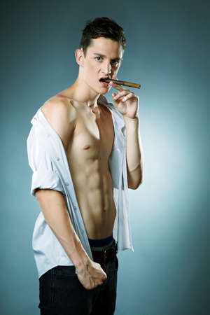 Young man posing in studio for fashion photos in style like boss with cigar.