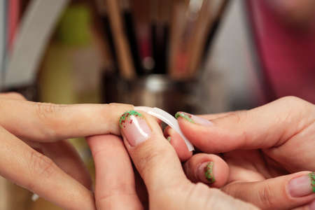 gels: Nail art - applying gels and colors in nail studio Stock Photo
