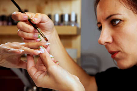 gels: Nail art - applying gels and colors in nail studio Stock Photo