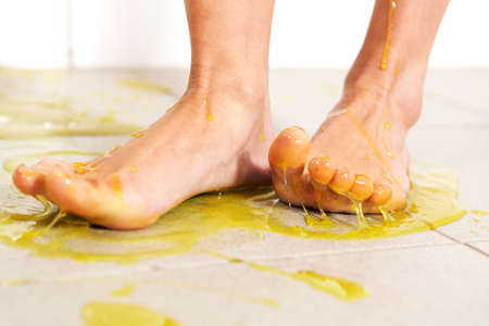 Young woman playing with melted Jelly in white tile room - detail of foot in jelly