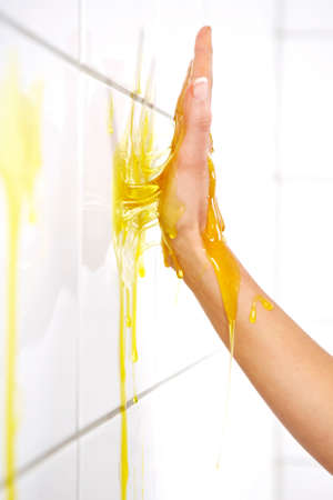 depraved: Young woman playing with melted Jelly in white tile room - detail of hand covered with jelly Stock Photo