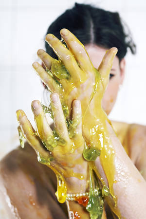 Young woman playing with melted Jelly in white tile room
