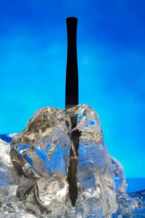 hypodermic: Plastic hypodermic frozen in ice block on the blue  Stock Photo