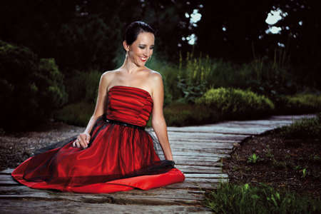 fashion photos: Lady in red dress posing on outdoor location in garden for fashion photos